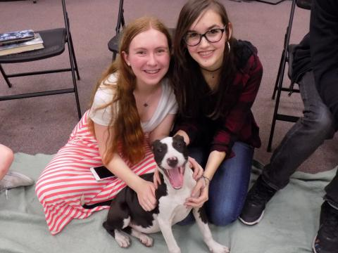 Two girls pose with a smiling puppy.