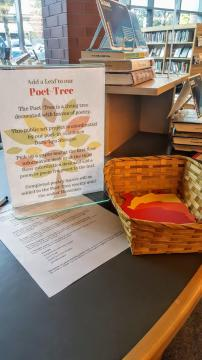 "A basket of paper leaves with a sign that reads ""add to our Poet-Tree"" with instructions on how to add a poem."
