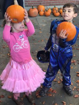 Two children holding pumpkins