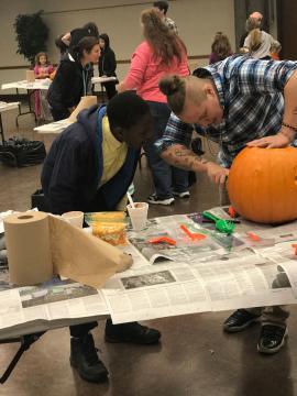 Two teens carving a pumpkin