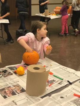 """A girl pulling out pumpkin """"guts"""""""