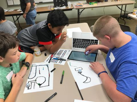 Three children playing with an Ozobot