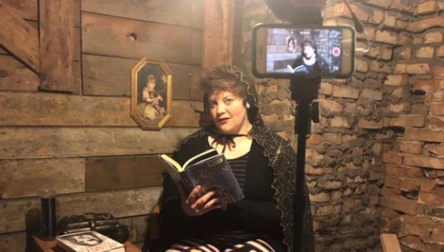 Photo of scary story teller reading a book in front of recording phone.