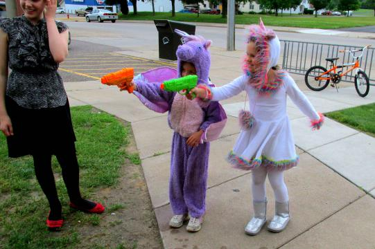Children dressed as superheroes shoot squirt guns at a target.