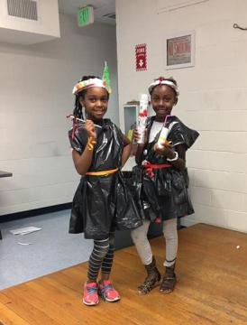 Two girls pose with their creations.