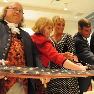 "Ribbon cutting for the opening of the ""Benjamin Franklin: In Search of a Better World"" traveling exhibition with Ben Franklin (Christopher Lowell); Julie McDaniel, and Sherry and Greg Stocksdale."
