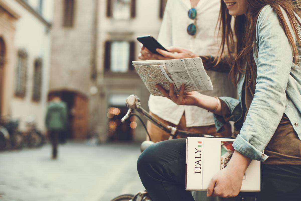 "Woman sitting on a bike holding a map and book that says ""Italy"""
